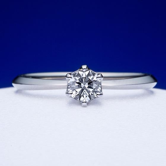 王道の1粒タイプの婚約指輪。アームの部分に一筋のラインを施すことでよりシャープに見せ、指をきれいに見せる効果があります。
