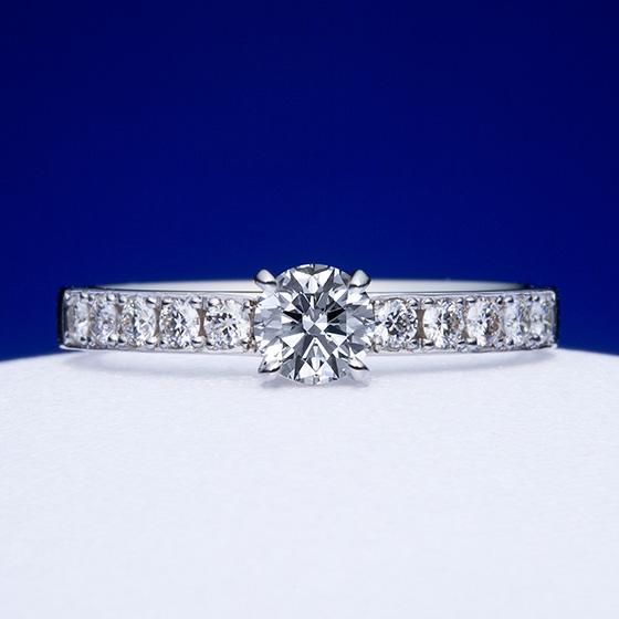 センターダイヤを強調するエタニティタイプの婚約指輪。まっすぐに敷き詰められ、ダイヤモンドの輝きが指いっぱいに広がる。