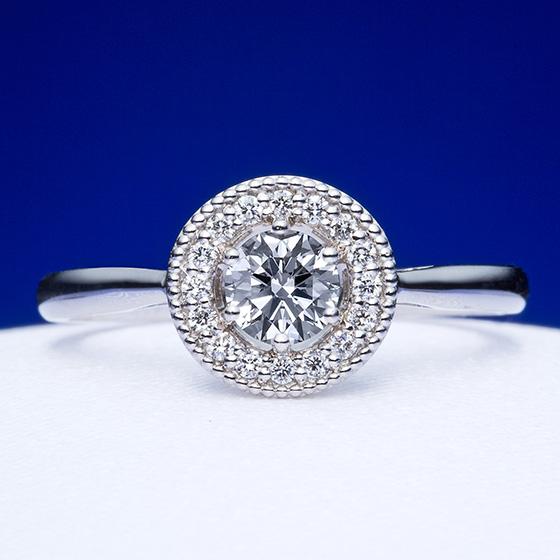 中心のダイヤモンドを取り囲んだ小さなダイヤモンド。サイドに施されたミル打ちがエレガントに彩ります。