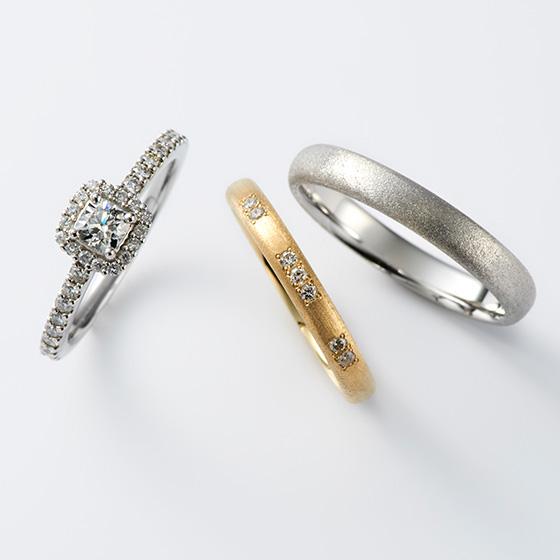 ダイヤモンドをダイヤモンドで囲ったゴージャスな婚約指輪。細身に仕上げていることでセットでつけてもオシャレに見える。