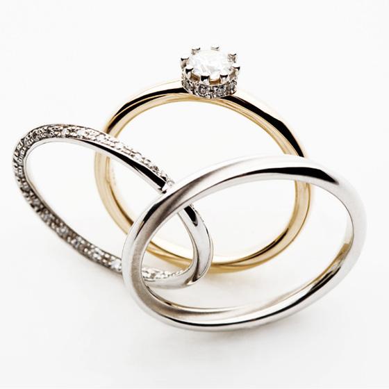 2人を繋ぐ、途切れることのない輪をイメージしたセットリング。婚約指輪にはダイヤモンドを支えるツメのサイドにダイヤモンドが…