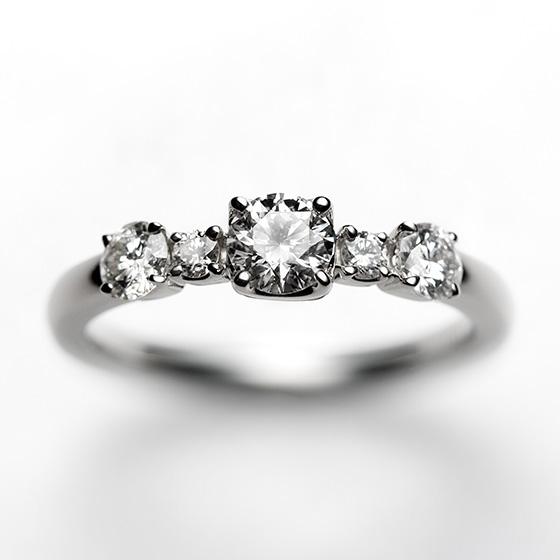1粒ずつ個性を持ったボンボンショコラのようにきらめきを放つ婚約指輪。様々に大きさをかえたダイヤモンドが寄り添い、丸みのある愛らしいデザインに仕上げました。
