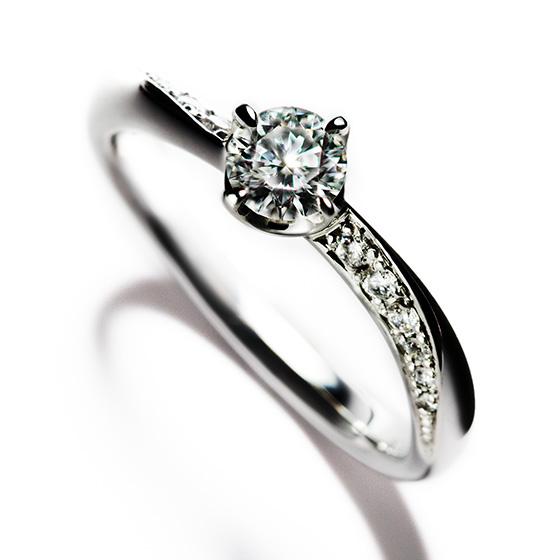 天使の羽のようにやさしくうつくしいS字ラインを描いたエンゲージリング。カーブラインをつけることでメレダイヤモンドが大きく留められ、ゴージャスな雰囲気にも。