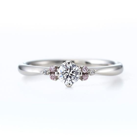 メインのダイヤモンドを彩る、3ピースのメレダイヤモンド。ピンク色のダイヤモンドがブーケのようで、かわいらしい印象に。