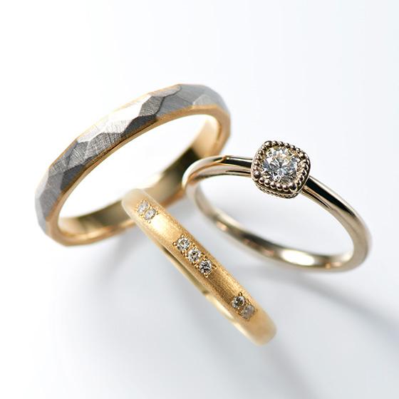 ミル打ちに囲まれたアンティーク調の婚約指輪。同じゴールドでそろえた結婚指輪はつや消し加工をしており、落ち着いた雰囲気に。