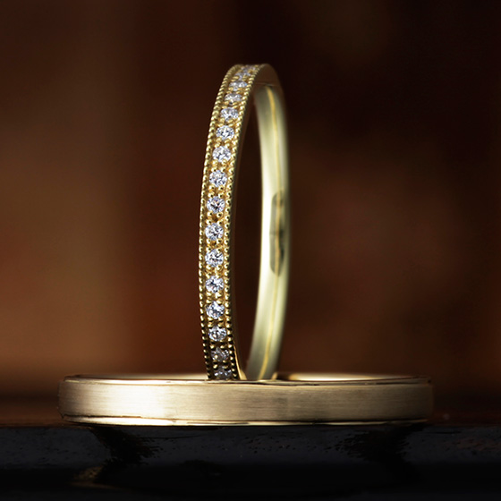 細身のリングに細かなダイヤモンドと、ミル打ちが上品な印象。men'sリングもストレートに艶消し加工がかっこよく、大人な男性を思わせる。