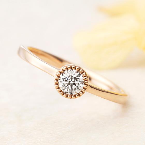 シンプルな1粒タイプのエンゲージリング。ダイヤモンドを包み込むミル打ちが優しい印象を作り出す、想いを込めた婚約指輪です。
