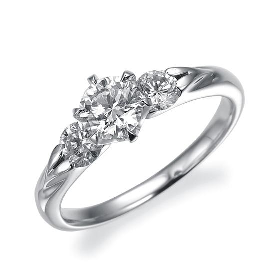 両サイドのメレダイヤがセンターダイヤと絶妙にシンクロし、贅沢感のある美しさを醸し出したデザインです。脇のダイヤの横はハートフォルムが施された枠になっております。