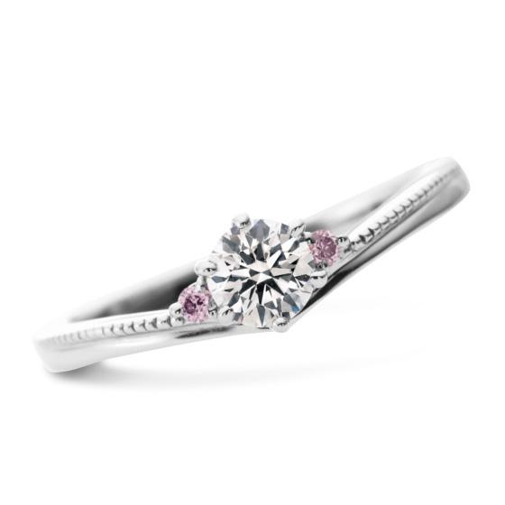 流れるような緩やかなカーブラインを描いた、女性らしいエンゲージリング。サイドに小さく留めたピンク色のダイヤモンドがふたりの間に秘められた永遠の証。