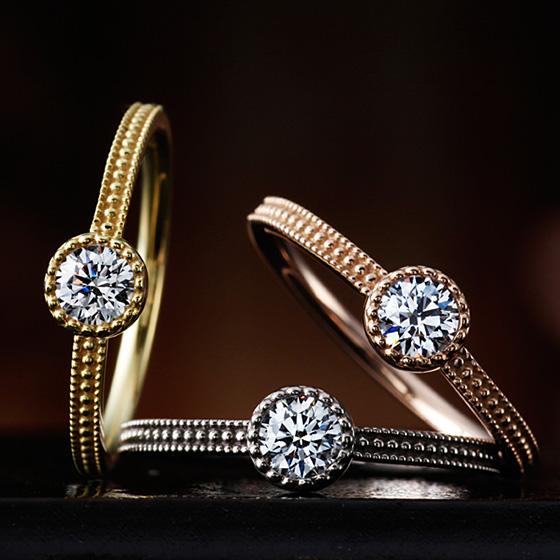 ミル打ちを施したアンティーク調の婚約指輪。埋め込みのデザインはシンプルに、普段使いもしやすい。