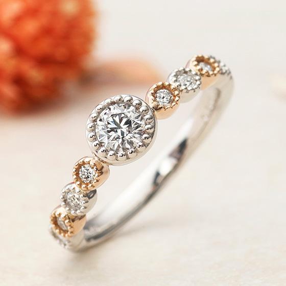 きらきらと輝く宝石たちに囲まれたキュートなエンゲージリング。