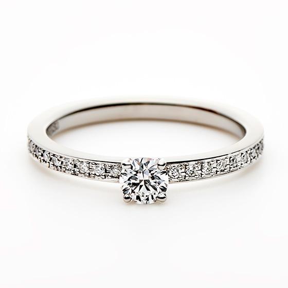お指全体が輝くエタニティタイプのエンゲージリング。メインのダイヤモンドが一段高くなっているため、存在感を出したつくりになっている。