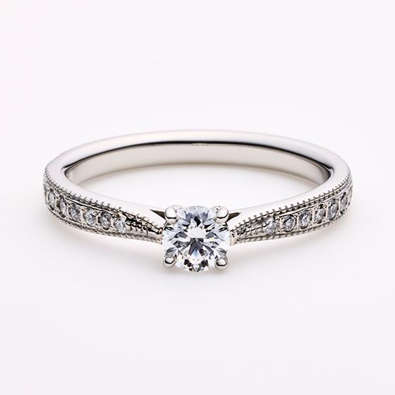 ミルグレインが上下に施されたエレガントなデザイン。中央に向かい、絞りがあることで指をきれいにみせダイヤモンドも大きく見せる効果もある。