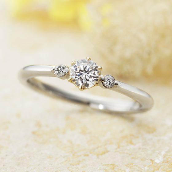 センターダイヤモンドの台座の色合いを変えたエンゲージリング。サイドビューでは花弁のデザインをしており、キュートな印象に。