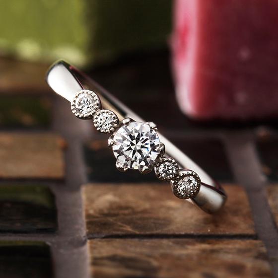 ミル打ちで囲まれたダイヤモンドが愛らしい婚約指輪。風船をイメージしました。