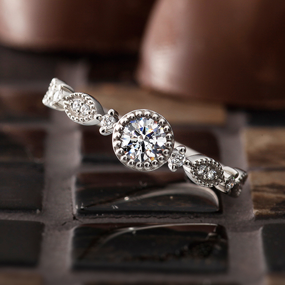 ミル打ちで囲まれたデザインと、ダイヤモンドが華やかな印象を作り出す婚約指輪です。