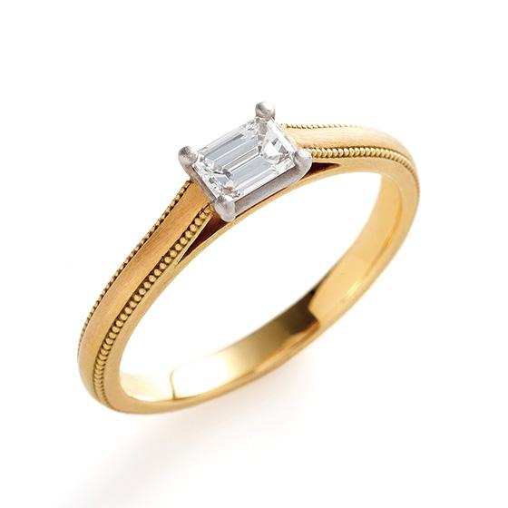 シンプルなストレートタイプのエンゲージリング。エメラルドカットのダイヤモンドがよりシャープな印象を与えてくれる。