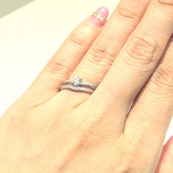 >V字カーブが重なり、指全体を華奢に演出。メレダイヤが一体となってセンターダイヤを際立たせてくれる♡