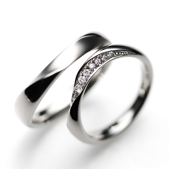 ボリュームのあるリングにひねりとカーブを加えた結婚指輪。大粒のダイヤモンドを使用し、華やかな印象を与える。
