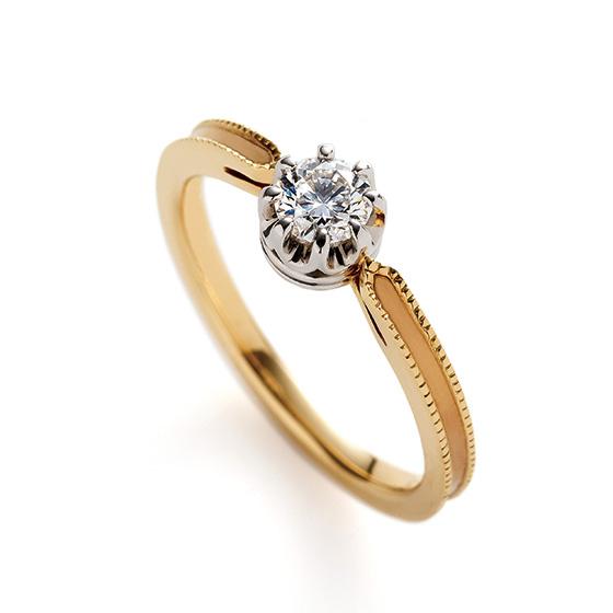 王冠のモチーフデザインが、ゴールドの色味と相まってアンティークのイメージを作り上げたエンゲージリング。