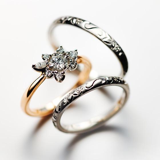鮮やかに咲き誇る華やかな印象の婚約指輪と、1周彫模様を施した結婚指輪。