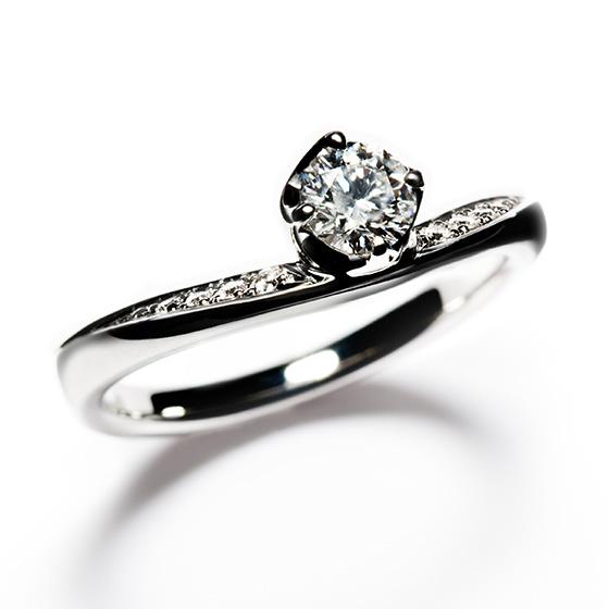 タルト生地に優しく包まれたような、ダイヤモンドが美しい婚約指輪。ふたりの永遠の愛と誓いを込めた強い意志が感じられるデザインです。