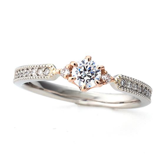 中央のダイヤモンド部分をゴールドの爪で留めた婚約指輪。華やかな印象の中に色味を変えることでメインのダイヤモンドの印象を強くさせるデザインです。
