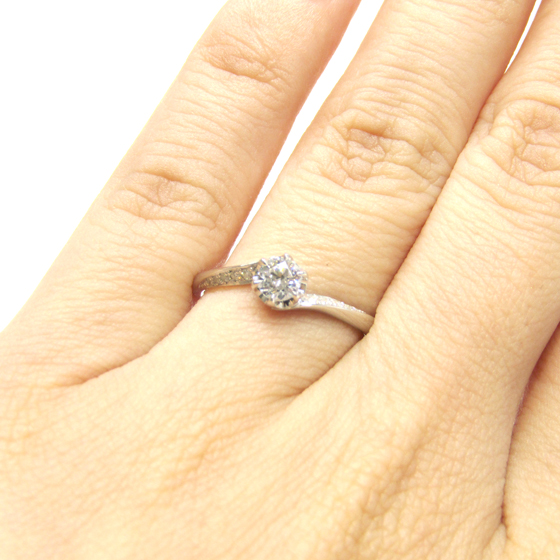 >メレダイヤのラインが、センターダイヤを上下から包みこみ立体的なフォルムに。指長効果もあり♡