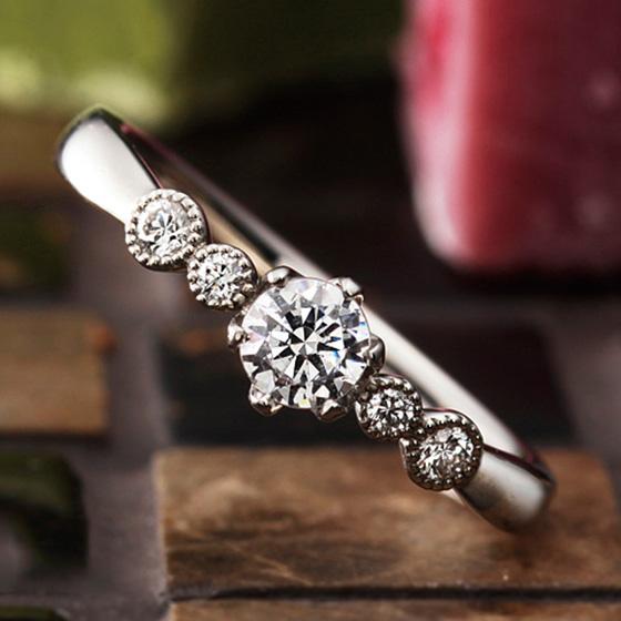 ミル打ちで囲まれたダイヤモンドが愛らしい婚約指輪。