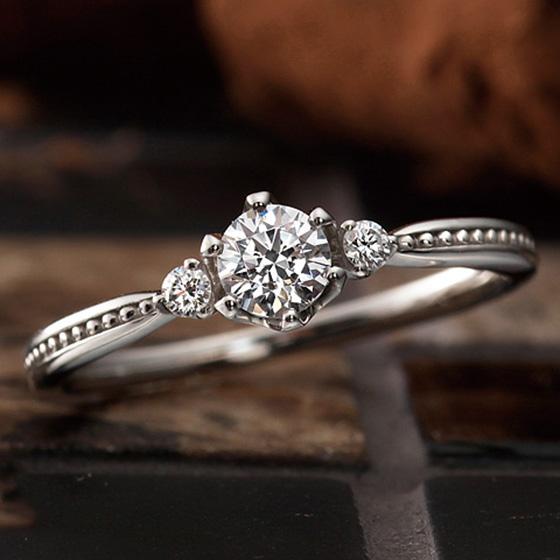両サイドにダイヤモンドを留め、ミル打ちでアレンジした婚約指輪。モダンで華やかな印象に。