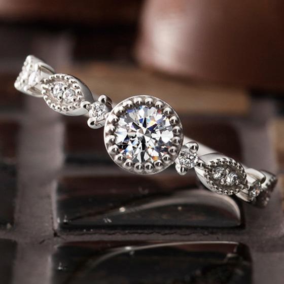ミル打ちで囲まれたデザインと、ダイヤモンドが華やかな印象を作り出すエンゲージリング。