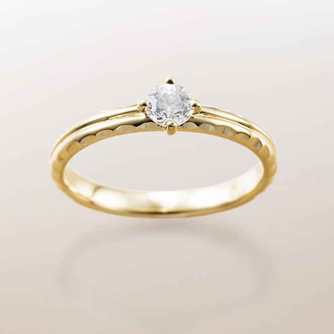 サイドカットにダイヤモンドカットが施された婚約指輪。ハワイアンジュエリーの結婚指輪との重ね付けもお楽しみいただけます。
