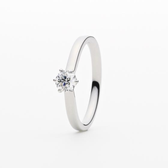 大きなダイヤモンドを支える石座に、2つのメレダイヤモンドを埋め込んだサイドビューも楽しめるエンゲージリング。