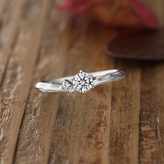 お指をきれいに見せてくれるVラインの婚約指輪(エンゲージリング)アシメントリー(左右非対称)なデザインが特徴的です。