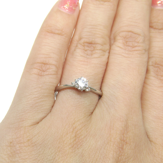 中心のダイヤモンドの両サイドに寄り添う2石のメレダイヤモンドがキュート。S字ウエーブが指のラインをきれいに見せてくれる婚約指輪。