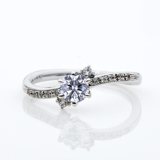 6本爪がダイヤモンドを丸く美しく演出。腕には左右5石ずつ、中心のダイヤモンドの両サイドには1石ずつメレダイヤモンドがあしらわれたゴージャスな印象の婚約指輪