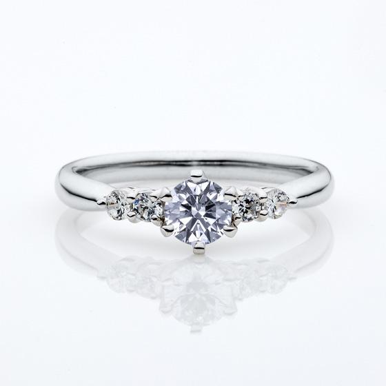 ストレートタイプにメレダイヤモンドが4石輝いたさりげなくゴージャスな婚約指輪。華やかなデザインがお好みの方におすすめです。