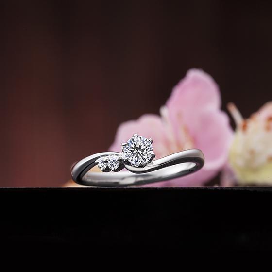 中心ダイヤモンドのサイドにメレダイヤモンドが2粒施された可愛らしいデザインの婚約指輪です。