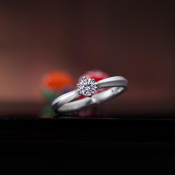 中心ダイヤモンドに向かってボリュームを抑えたダイヤモンドがより引き立つデザインの婚約指輪です。