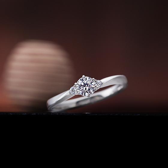 中心のダイヤモンドのサイドにメレダイヤモンドをあしらった可愛らしいデザインの婚約指輪です。
