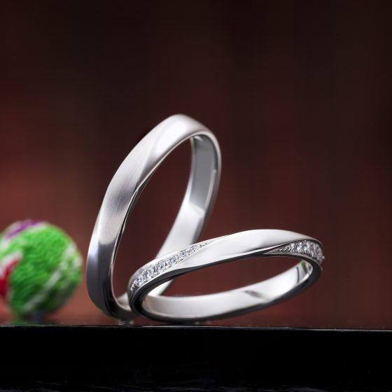 ストレートタイプのに斜めに流れるようにデザインの入った結婚指輪(マリッジリング)両サイドにメレダイヤモンが入ってさりげなくゴージャス。