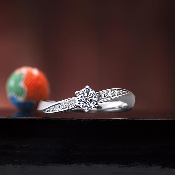 流れるようにセットリングされたメレダイヤモンドが中心のダイヤモンドに向かって輝く贅沢なデザインの婚約指輪です。