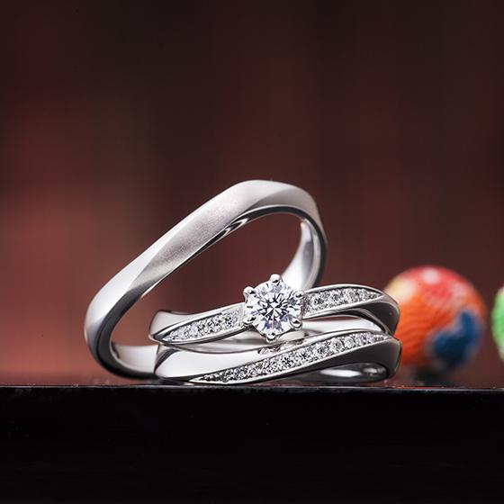 メレダイヤモンドが流れるようにキラキラ輝く可愛らしいデザインのセットリング。