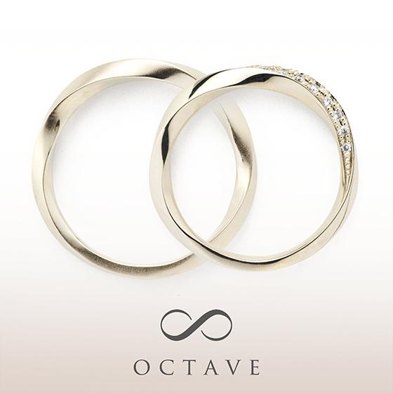 全体的にひねってあるような個性的な結婚指輪(マリッジリング)。レディースには流れるようにメレダイヤモンドが入っています。