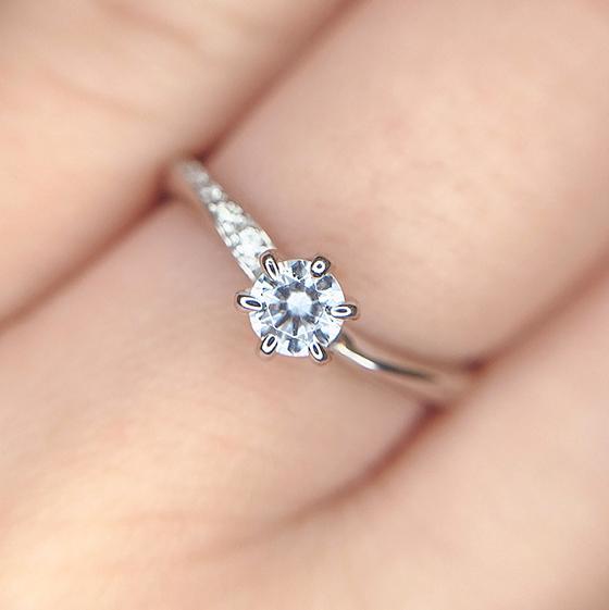 カーブやメレダイヤモンドのセットが左右非対称にデザインされた婚約指輪。微妙なデザインを楽しむことが出来ます。