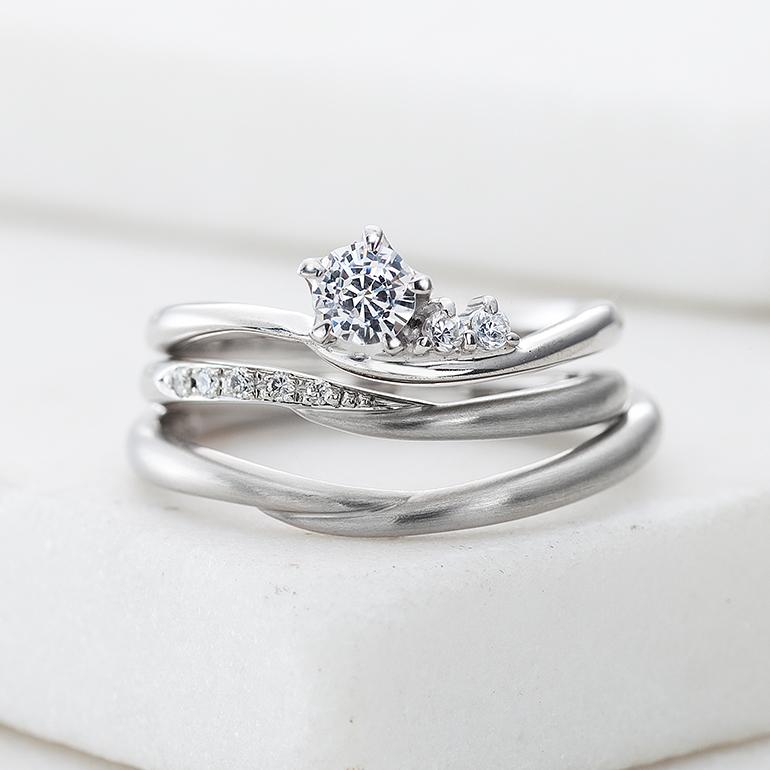 二人の手がそっと重なり合うようなデザイン。華奢なリングが指を綺麗に見せてくれます。