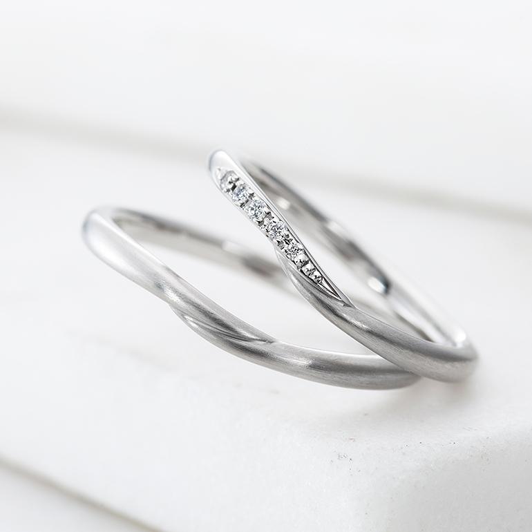 まっすぐでシンプルなデザインの結婚指輪。重なり合ったアームが2人の絆を表現します。