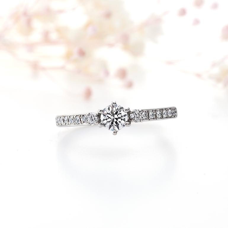 ハーフエタニティタイプのゴージャスな婚約指輪。両脇1石づつ少し大きめなメレダイヤモンドが特徴