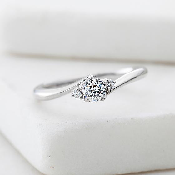 華奢なアームに、中心ダイヤがよく目立つエンゲージリング。指が細く見えるデザインです。