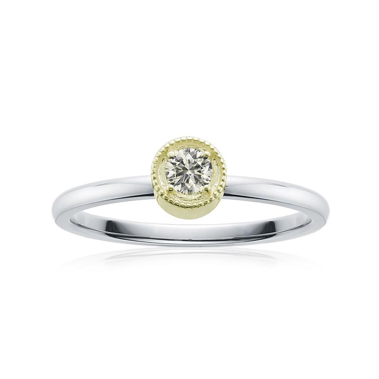 ダイヤモンドの周りを繊細なミル打ちが施されたイエローゴールドの台座のプロポーズリング